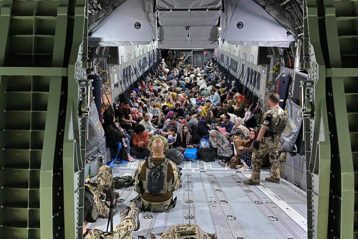 Un aereo con rifugiati afgani insieme uomini dell'esercito