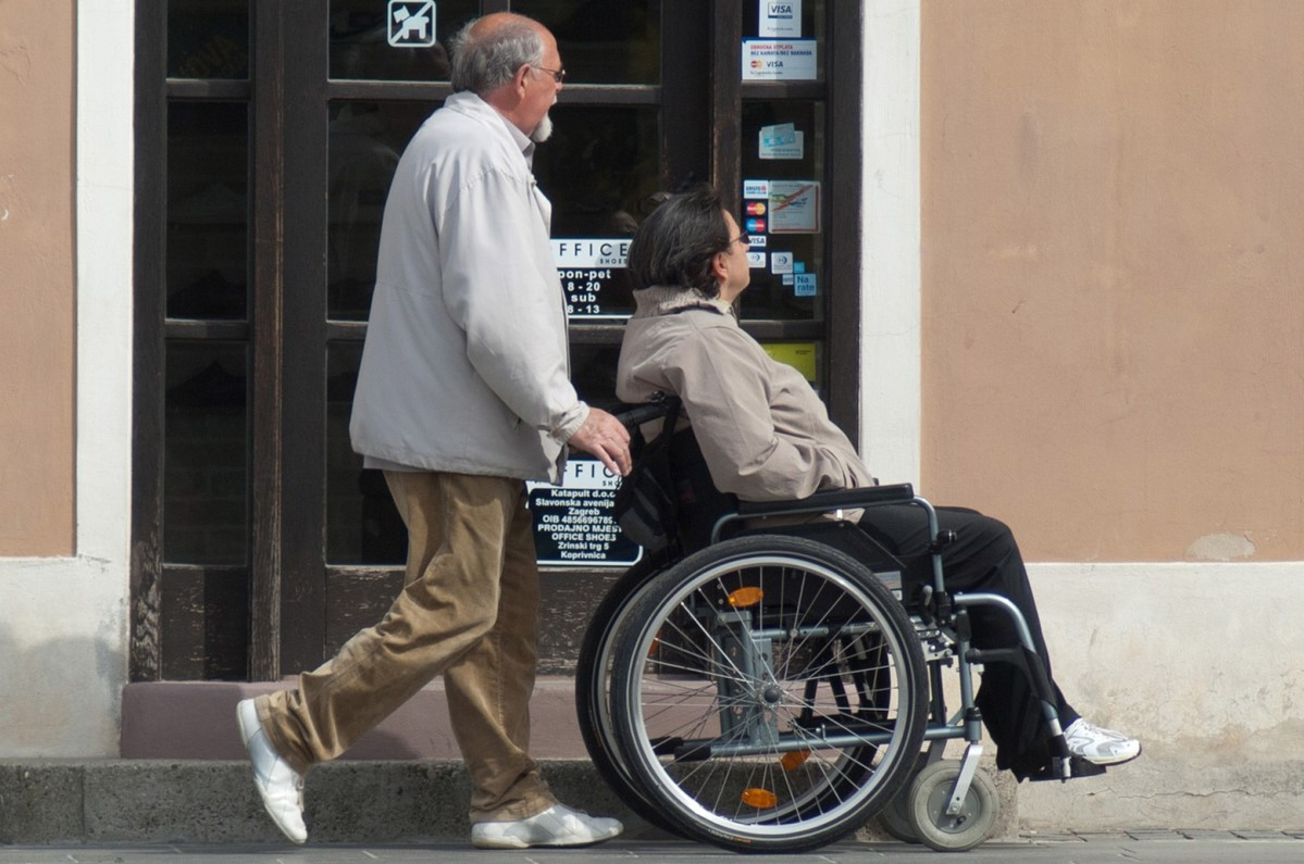 Familiare spinge una carrozzina per disabile