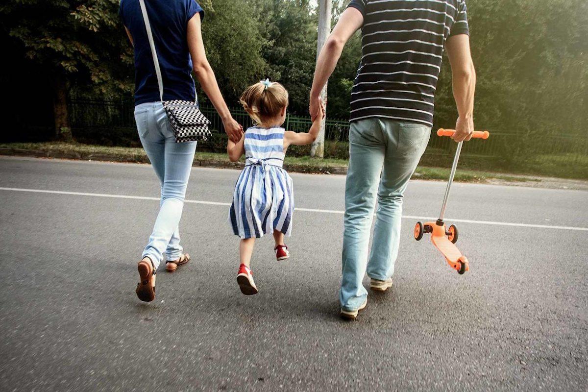 Una bambina attraversa la strada con i genitori